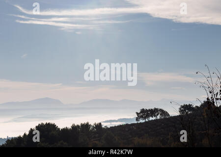 Fog filling a valley in Umbria (Italy), with layers of mountains and hills and various shades of blue. - Stock Image