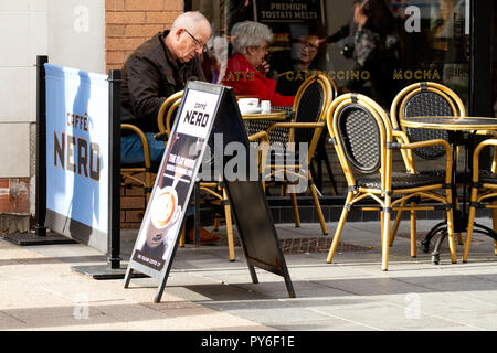 An middle-aged man sitting outside the Cafe Nero while two elderly women are sitting together inside deciding what coffees to order in Dundee, UK - Stock Image