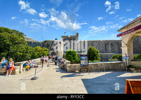 The outer city Pile Gate and stone bridge leading to the ancient walled city of Dubrovnik, Croatia with tourists enjoying a sunny summer day - Stock Image