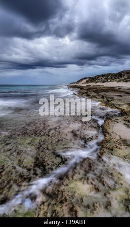 Stormy skies over the limestone coastline at Burns Beach. - Stock Image