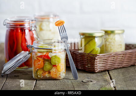 Autumn seasonal pickled vegetables in glass jars, on rustic wooden background. - Stock Image