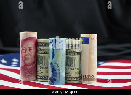 National currencies from China, United States, Canada, and European Union placed on American flag  reflect global nature of business - Stock Image