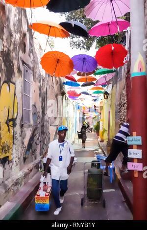 Cartagena Colombia Old Walled City Center centre Getsemani Callejon Angosto Calle 27 narrow street hanging colorful umbrellas installation Hispanic Bl - Stock Image