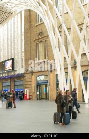 Passengers wait for a train in Kings Cross railway station, London, UK - Stock Image