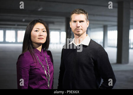 Caucasian male and Asian female business owners in a new raw business space. - Stock Image
