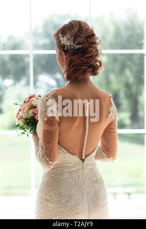 Bride with bouquet by window - Stock Image