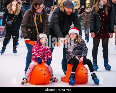 Edinburgh, Scotland, United Kingdom,  8th November 2018. Christmas celebrations: A busy Saturday in the capital city centre at Edinburghs Christmas celebration venue. Families enjoy the ice skating rink in St Andrew Square Gardens. Children being pushed on seal ice aids - Stock Image