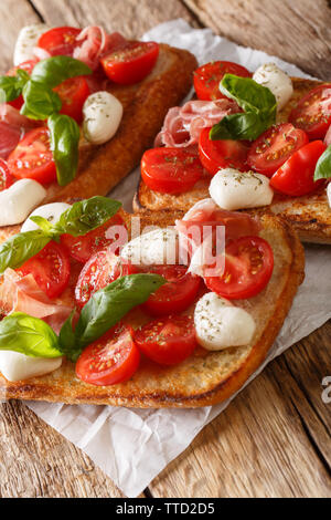 Homemade toasts with mozzarella, tomatoes, prosciutto and basil close-up on the table. vertical - Stock Image