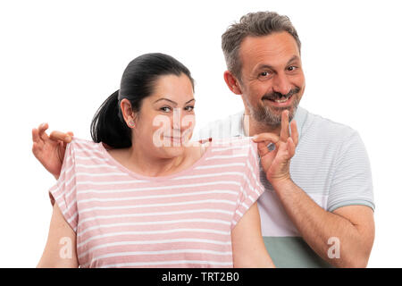 Smiling man presenting girlfriend pink tshirt by holding it with fingers isolated on white studio background - Stock Image