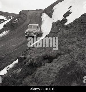 1950s, Vanguard motorcar parked on a snowy hillside in winter, England, UK. - Stock Image