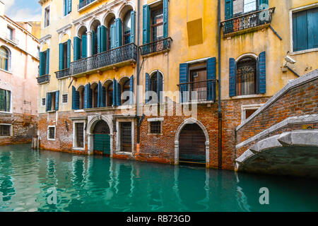 A typical, picturesque and colorful residential canal in the historic center of Venice, Italy with emerald green water. - Stock Image
