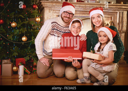 Happy family in Santa caps looking at camera by Christmas tree - Stock Image