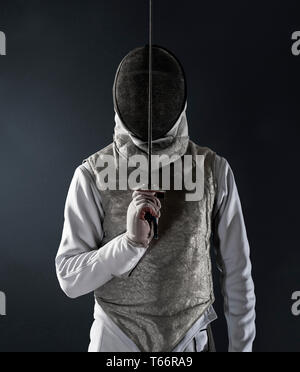Portrait man in fencing uniform and mask - Stock Image