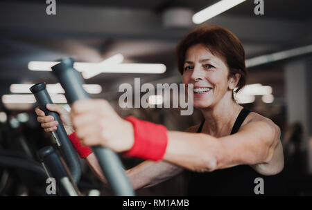 A cheerful female senior in gym doing cardio workout. - Stock Image