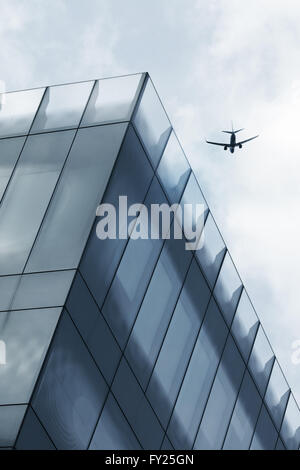 Aircraft flying over office tower - Stock Image