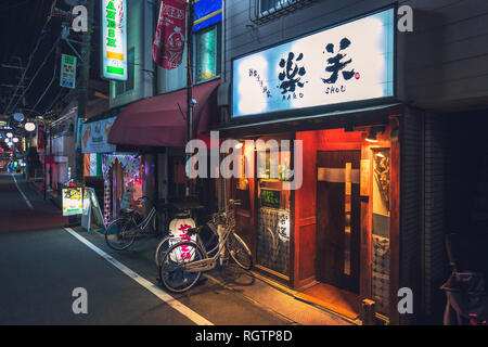 Illuminated facade of a typical small Japanese restaurant, Sone Nishimachi, Toyonaka, Japan - Stock Image