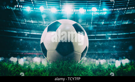 Close up of a soccer ball in the center of the stadium illuminated by the headlights - Stock Image