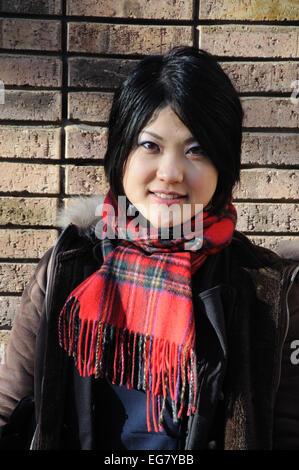 Japanese woman wearing tartan scarf, England, UK - Stock Image