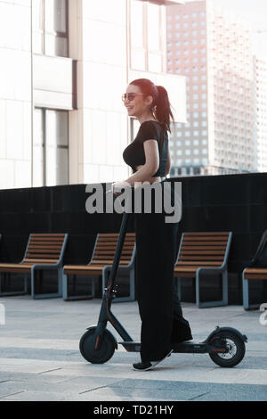 Young attractive woman riding electrick kick scooter at modern cityscape. - Stock Image