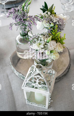 flowers arrangement and decoration rustic interior design in wedding table detail - Stock Image