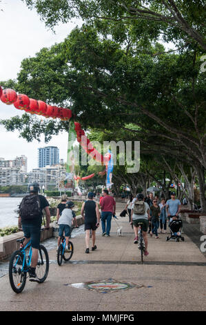 Cyclists and pedestrians share a riverside promenade on South Bank, Brisbane, Queensland, Australia - Stock Image