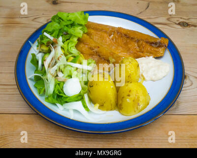 A smoked Mackerel  salad with new potatoes and horseradish sauce on a blue and whit plate on a wooden table top. - Stock Image