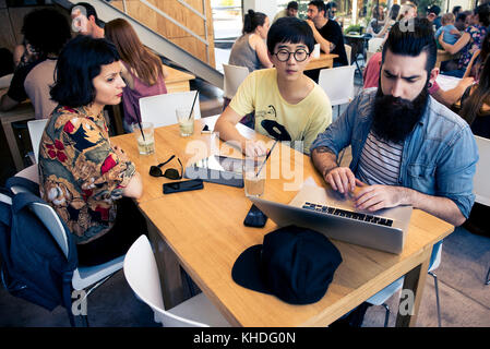 Man using laptop computer while companions watch - Stock Image
