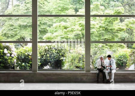 Two businessmen working on a notebook computer and sitting in front of a large window in the lobby of a convention center. - Stock Image
