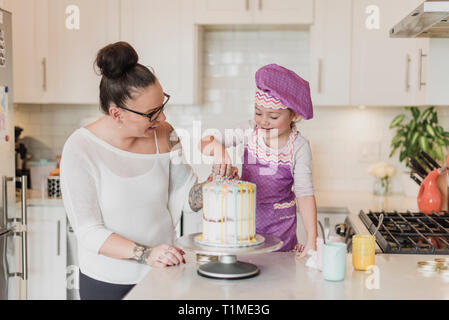 Mother and daughter decorating cake in kitchen - Stock Image