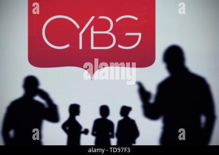 The CYBG logo is seen on an LED screen in the background while a silhouetted person uses a smartphone in the foreground (Editorial use only) - Stock Image