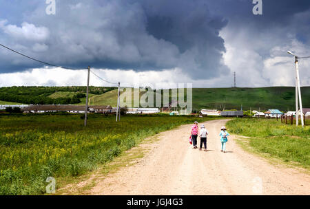 Three young girls walk along a dusty road towards ominous rain cloud storm ahead - Stock Image