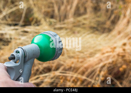 Garden hosepipe spray gun - as metaphor for 2018 heatwave and drought, and hosepipe ban. [Photographer's hand in shot - use without MR form]. - Stock Image