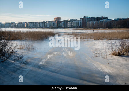Scenic View Of Frozen River Against Cityscape During Winter - Stock Image