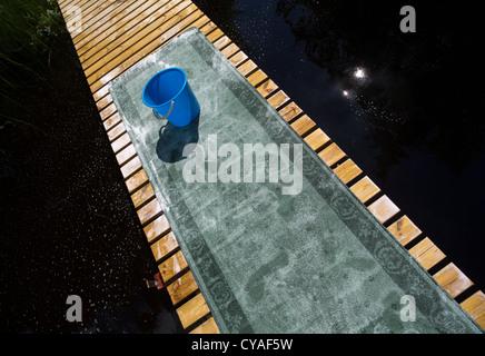 Washing carpet at jetty at Summer - Stock Image