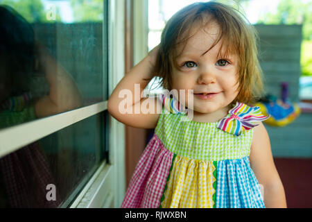 A toddler girl  wearing a rainbow sun dress smiles at the camera in a close up photo. - Stock Image