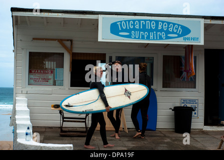 Female surfers in wetsuits with surf board outside a surf hire kiosk at Toicarne Beach in Cornwall - Stock Image