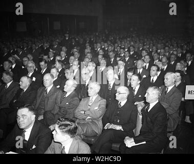 Men in a crowd listening intently ca. 1935 - Stock Image