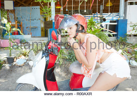Young woman putting on helmet by moped - Stock Image