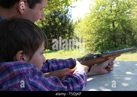 Father teaching his child to shoot a gun - Stock Image