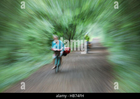 Two cyclists a man and a woman on a cyclepath taken with a long exposure whilst zooming to give the impression of - Stock Image