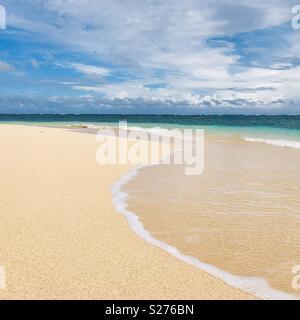 Waves rolling on shore on an empty beach. Tavarua island, Fiji. - Stock Image