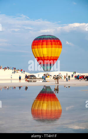 Hot air balloon reflected on puddle and people, White Sands Hot Air Balloon Invitational, White Sands National Monument, Alamogordo, New Mexico USA - Stock Image