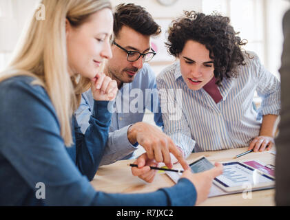 A group of young businesspeople with smartphone and laptop working together in a modern office. - Stock Image