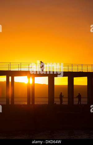 A couple walk along Whitby West Pier at sunset. - Stock Image