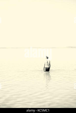 Man in swimming shorts walks into a calm serene lake in summer - Stock Image