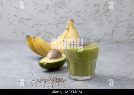 smoothies avocado banana in a glass, bananas and avocados, chia seeds on a gray concrete background - Stock Image