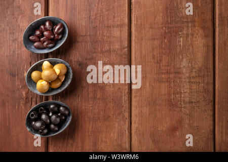 Olives in bowls, shot from the top on a dark rustic wooden background with copy space. Purple, green almond stuffed, and black pitted olives - Stock Image