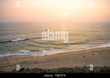 View from above, stunning aerial view of a beautiful tropical beach with people sunbathing and enjoying a beautiful sunset. Varkala, Kerala, India. - Stock Image