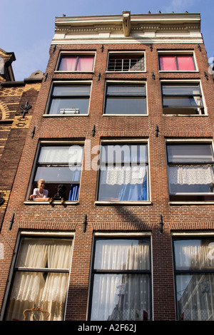 Amsterdam Jourdan woman with dog at window typical architecture - Stock Image