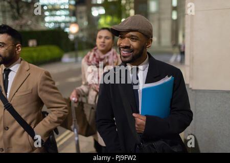 Smiling businessman walking on urban sidewalk at night - Stock Image